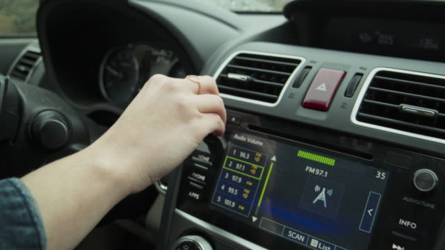 close up of hand of car driver adjusting radio station while driving / cedar hills, utah, united states - radio studio stock videos & royalty-free footage