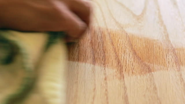 Close up of hand polishing wood