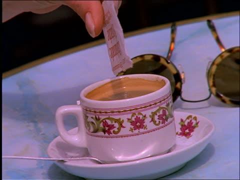 close up of hand putting sugar into and stirring espresso / Paris