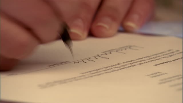 vidéos et rushes de close up of hand signing document - feuille papier
