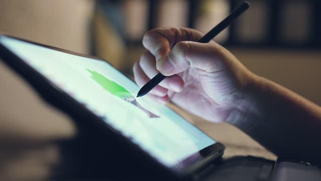 vidéos et rushes de fermez-vous vers le haut de la main utilisant le dessin numérique de crayon sur la tablette numérique - utiliser une tablette numérique