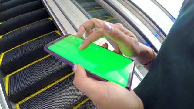 vídeos de stock, filmes e b-roll de close-up da mulher de mão usando um smartphone com tela verde em shopping center - mercado espaço de venda no varejo