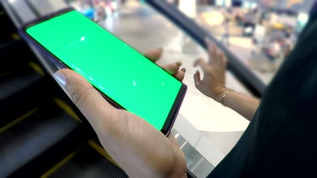 vídeos de stock, filmes e b-roll de feche acima da mulher da mão que usa um smartphone com a tela verde na alameda de compra - mercado espaço de venda no varejo