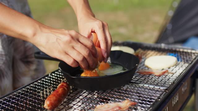 vidéos et rushes de fermez-vous vers le haut des mains craquant un oeuf dans une poêle sur un barbecue - activité de plein air