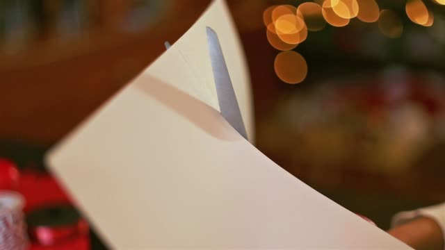 close up of hands cutting a piece of paper with scissor. - cutting stock videos and b-roll footage
