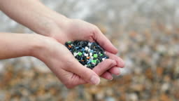 Close Up Of Hands Holding Plastic Granules Polluting Beach