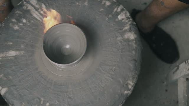 nahaufnahme von händen eines töpfers, erstellen eine tasse auf dem kreis-rad mit feuer spray-schaum-stock video - lehm mineral stock-videos und b-roll-filmmaterial