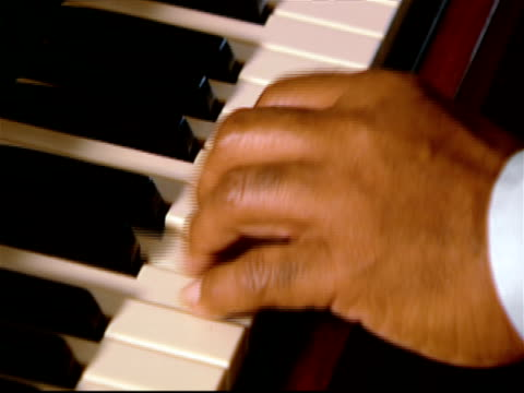 Close up of hands of elderly man playing organ