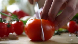 Close Up of Hands of Male Cook Cutting Tomato into Two Halves