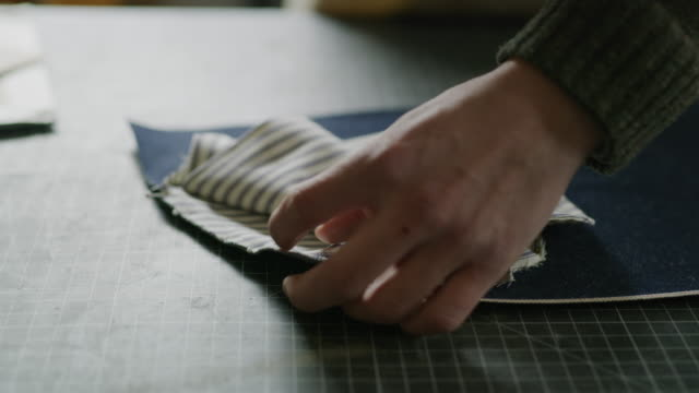close up of hands of man pinning fabric to leather in workshop / provo, utah, united states - provo video stock e b–roll