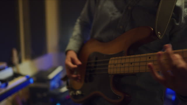 stockvideo's en b-roll-footage met close up of hands of man playing bass guitar in music studio / provo, utah, united states - provo