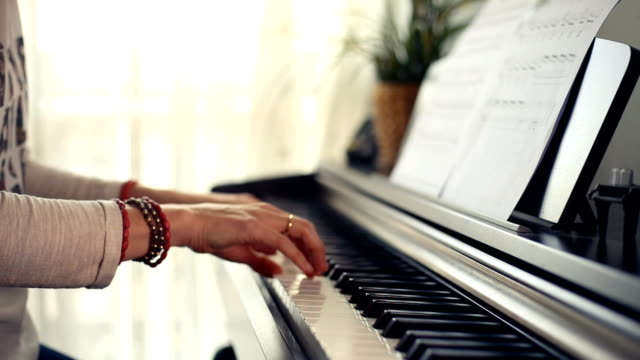 stockvideo's en b-roll-footage met close up of hands playing the piano keys gently - una sola mujer