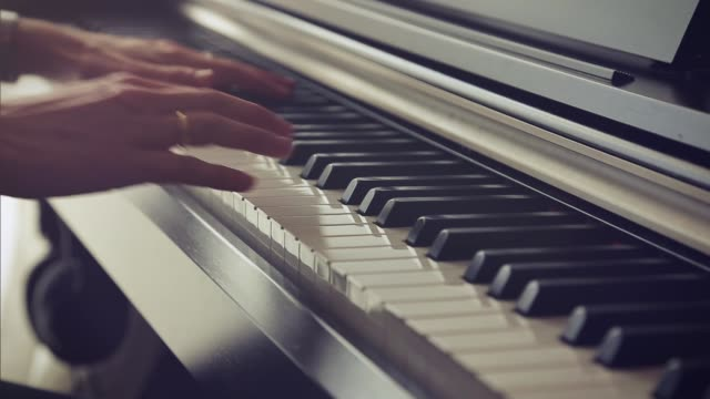 Close up of hands playing the piano keys.