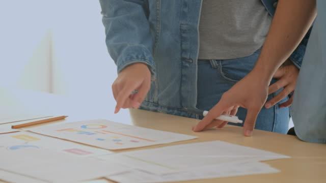 vídeos de stock, filmes e b-roll de feche acima das mãos que apontam no documento e que discute a solução do projeto na reunião da equipe no escritório, brainstorming do colega de trabalho ao sucesso no conceito do negócio - mostrar