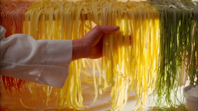 close up of hands removing linguine from pasta drying rack - drying rack stock videos and b-roll footage