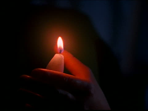 stockvideo's en b-roll-footage met close up of hands shielding candles as they light other candles - stroomuitval
