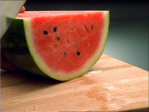 close up of hands slicing watermelon with knife