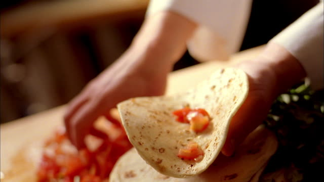 close up of hands sprinkling chopped tomatoes in flour tortillas - tortilla flatbread stock videos & royalty-free footage