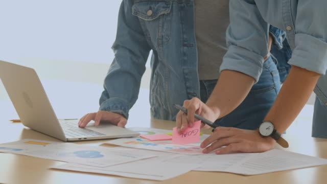 vídeos de stock, filmes e b-roll de feche acima das mãos que escrevem no documento ao discutir a solução do projeto na reunião da equipe no escritório, brainstorming do colega de trabalho ao sucesso no conceito do negócio - papel