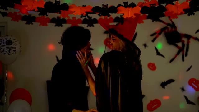 stockvideo's en b-roll-footage met close-up van geluk man en vrouw dragen halloween kostuums dansen in het feest. lachende mensen in halloween kostuums vieren halloween party - graaf dracula