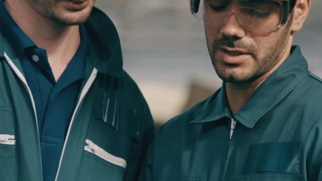 vidéos et rushes de fermez-vous vers le haut des ouvriers de happy factory discutant du travail utilisant la tablette dans la ligne d'usine, inclinez vers le bas à la tablette. moyen-orient et ethnie caucasienne. concept de fabrication. - manufacturing occupation