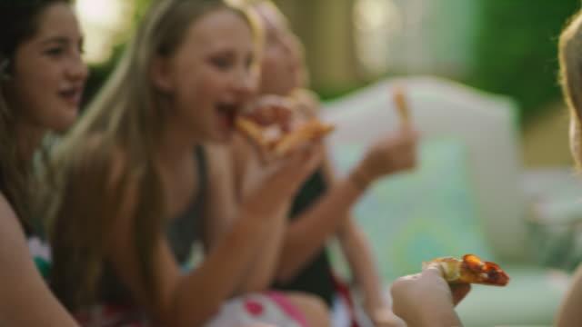 vídeos y material grabado en eventos de stock de close up of happy girls sitting poolside laughing and eating pizza / cedar hills, utah, united states - pizza