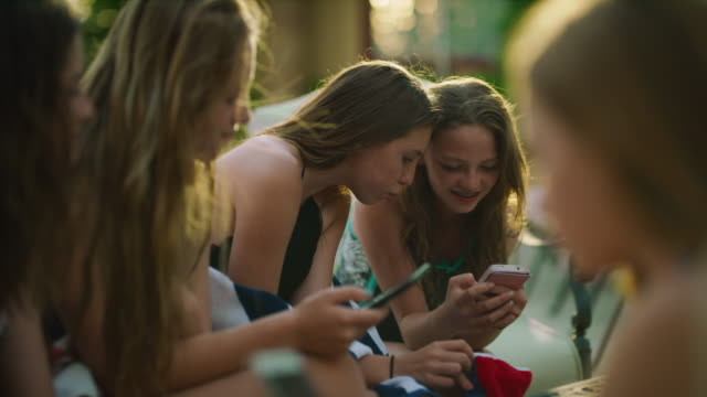close up of happy girls sitting poolside using social media on cell phones / cedar hills, utah, united states - social media stock videos & royalty-free footage