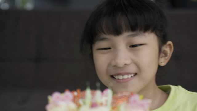 vidéos et rushes de fermez-vous vers le haut de la petite fille heureuse soufflant des bougies sur un gâteau d'anniversaire. - famille avec un enfant