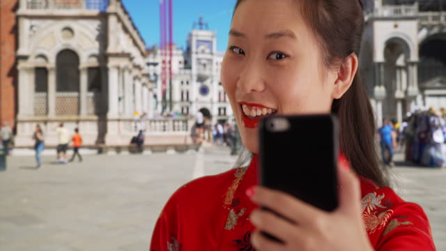 vídeos de stock e filmes b-roll de close up of happy millennial woman taking selfie with smartphone in venice italy - tradição