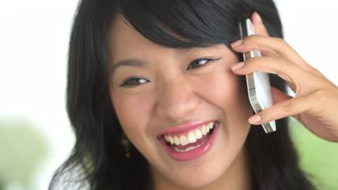 close up of happy woman laughing and talking on phone - endast unga kvinnor bildbanksvideor och videomaterial från bakom kulisserna
