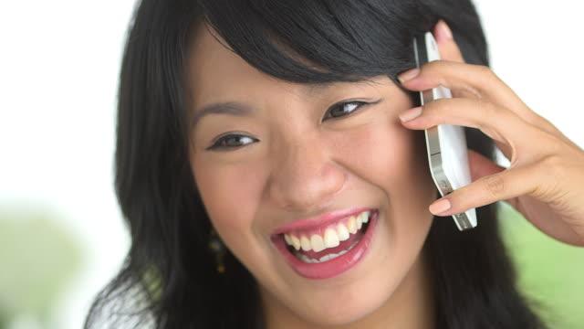 stockvideo's en b-roll-footage met close up of happy woman laughing and talking on phone - natuurlijk haar
