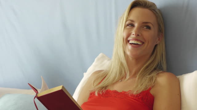 close up of happy woman reading book in bed/marbella region, spain - nur junge frauen stock-videos und b-roll-filmmaterial