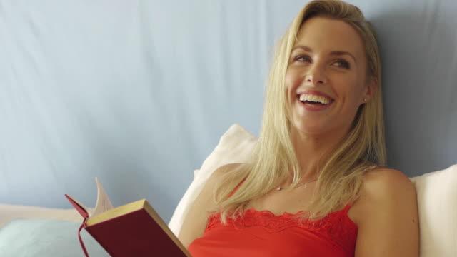 close up of happy woman reading book in bed/marbella region, spain - 若い女性だけ点の映像素材/bロール