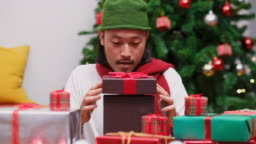 Close up of happy young asian man opening and surprising with Christmas present, gift box at celebration party, slow motion