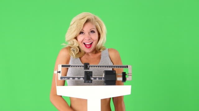 close up of happy young woman weighing self on scales - mass unit of measurement stock videos and b-roll footage