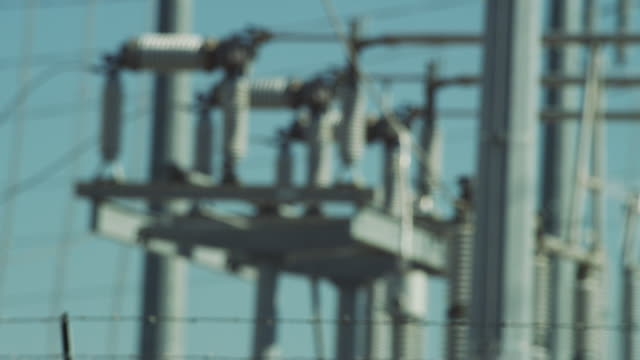 Close up of high voltage electrical wires and transformers at a power utility substation.