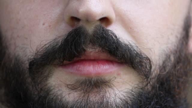 close up of hipster mustache waxing - 口ヒゲをひねる点の映像素材/bロール