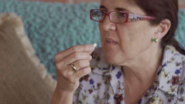 close up of hispanic mature woman taking medicine at home - antibiotic stock videos & royalty-free footage