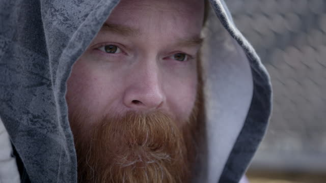 Close up of homeless mans face wearing hoodie