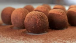 Close Up of Homemade Raw Vegan Energy Balls with Cocoa Powder Lying in a Row