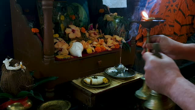 close up of human hand holding candle and playing brass bell during prayer in a temple - conch stock videos & royalty-free footage