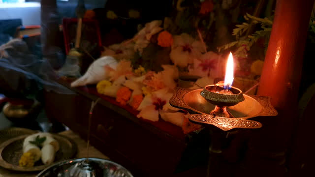 close up of human hand placing he candle and brass belll after finishing aarti (prayer) of hindu gods with hibiscus flowers, conch shell and joss stick (incense stick) with smoke at background - conch stock videos & royalty-free footage
