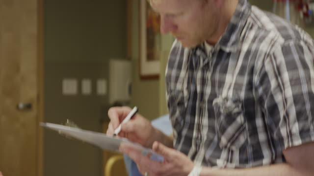 close up of husband with pregnant wife in hospital room writing on clipboard / midvale, utah, united states - delivery room stock videos & royalty-free footage
