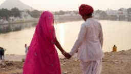Close up of Indian couple holding hands, woman wearing many traditional wedding bangles