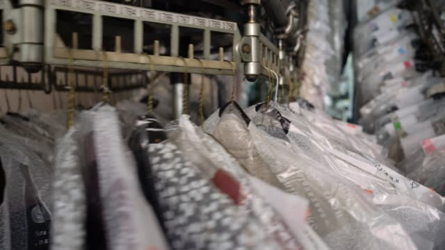 close up of industrial conveyor belt at an industrial laundry service with clothes hanging on it - laundry stock videos & royalty-free footage