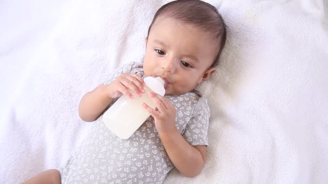close up of infant holding feeding bottle - powdered milk stock videos & royalty-free footage
