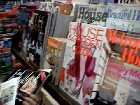 vídeos y material grabado en eventos de stock de close up of interior-design magazines on shelf in bookstore / pan to customer browsing through magazine, replacing on shelf and leaving with magazines / new york city - revista publicación