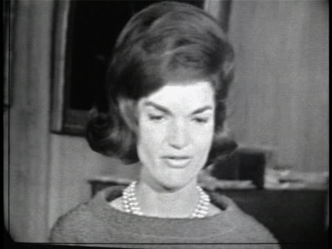 close up of jacqueline kennedy, who is standing in a room at the white house and wearing a dress and a pearl necklace. she has short hair. kennedy... - jackie kennedy stock videos & royalty-free footage