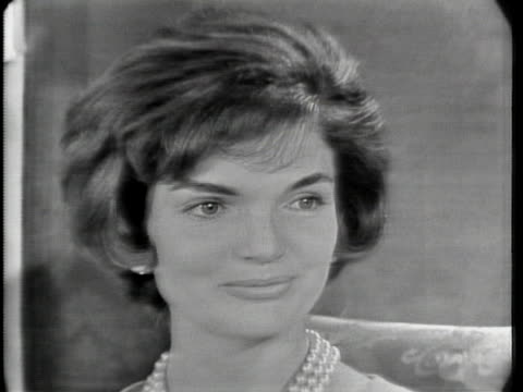 "close up of jacqueline kennedy's face as she sits in a chair. she has short hair and is wearing a pearl necklace. she says: ""the first thing i'd like... - curator stock videos & royalty-free footage"