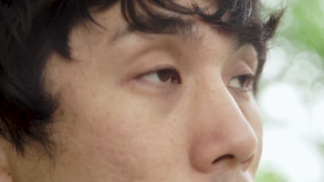 close up of japanese man eye on green background - blinking stock videos & royalty-free footage
